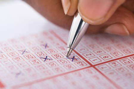Foto de Close-up Of Person's Hand Marking Number On Lottery Ticket With Pen - Imagen libre de derechos