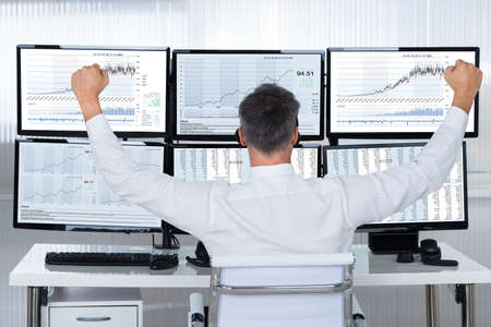 Foto de Rear view of successful stock market trader looking at graphs on multiple screens in office - Imagen libre de derechos
