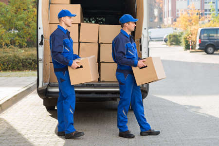 Photo for Smiling young delivery men carrying cardboard boxes while walking outside truck - Royalty Free Image