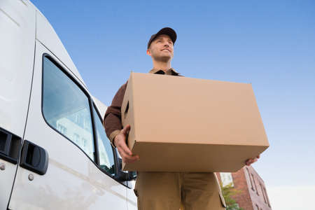 Photo pour Low angle portrait of young delivery man carrying cardboard box by truck against sky - image libre de droit