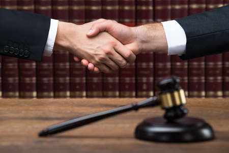 Foto de Gavel on wooden table with judge and client shaking hands in background at courtroom - Imagen libre de derechos