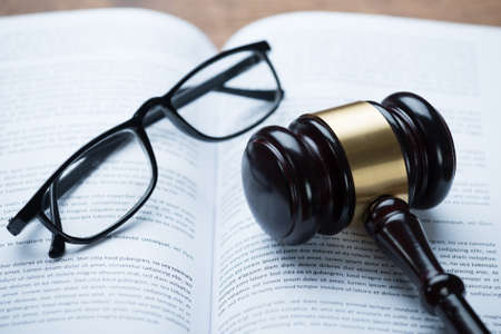 Photo pour High angle view of mallet and eyeglasses on open legal book in courtroom - image libre de droit