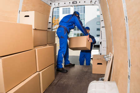 Foto per Young delivery men loading cardboard boxes in truck - Immagine Royalty Free