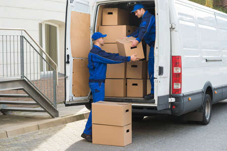 Photo for Young delivery men unloading cardboard boxes from truck - Royalty Free Image