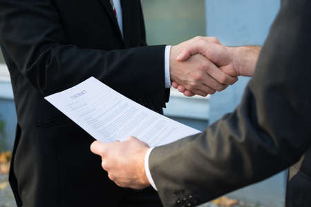 Photo pour Cropped image of businessman shaking hands with partner while holding contract papers - image libre de droit