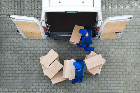 Photo for Directly above shot of delivery men unloading cardboard boxes from truck on street - Royalty Free Image