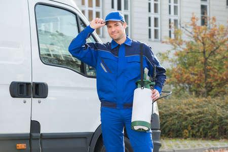 Foto de Portrait of happy pest control worker wearing cap while standing against truck - Imagen libre de derechos