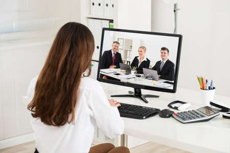 Photo for Rear view of young businesswoman attending video conference on computer in office - Royalty Free Image