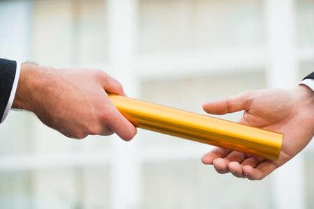 Photo pour Cropped hand of businessman giving golden relay baton to colleague outdoors - image libre de droit