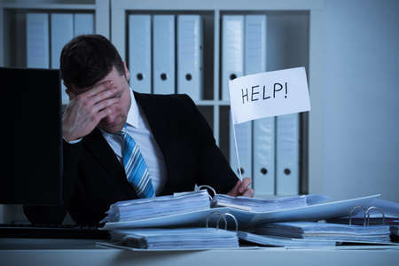 Photo pour Stressed accountant holding help sign at desk while working late in office - image libre de droit