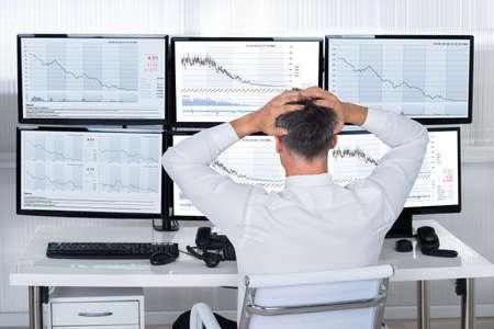Foto de Rear view of stock trader with hands on head looking at graphs on screens - Imagen libre de derechos