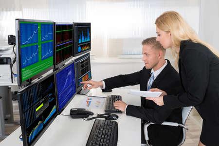 Foto de Young financial agents monitoring computer screens at desk in office - Imagen libre de derechos