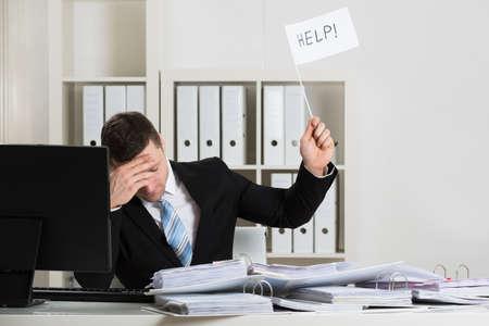 Foto de Overworked accountant holding help sign while working at desk in office - Imagen libre de derechos