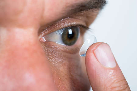Photo for Closeup of man putting contact lens in eye over white background - Royalty Free Image