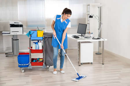 Photo pour Full length portrait of happy female janitor mopping floor in office - image libre de droit