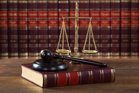 Foto de Closeup of mallet and legal book with justice scale on table in courtroom - Imagen libre de derechos