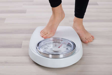 Foto de Low Section Of Person Standing On Weighing Scale - Imagen libre de derechos