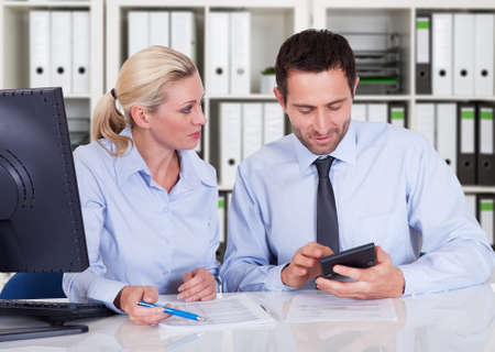 Photo pour Male and female accountants calculating finance together at desk in office - image libre de droit