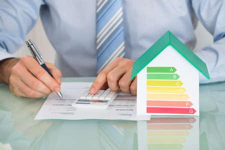 Foto de Close-up Of Businessman Calculating Energy Efficiency Rate Of House In Office - Imagen libre de derechos