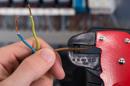 Photo pour Close-up Of Electrician Hands Stripping Electrical Wires - image libre de droit