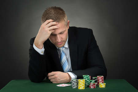 Foto de Depressed Male Poker With Chips And Cards On Table - Imagen libre de derechos