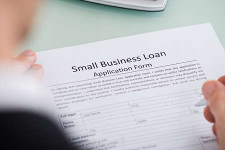 Photo pour Close-up Of Person Hand Over Small Business Loan Application Form - image libre de droit