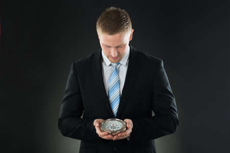 Portrait Of Young Businessman Holding Compass On Black Background