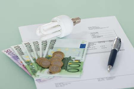 Foto de Close-up Of A Fluorescent Light Bulb With Invoice And Currency - Imagen libre de derechos