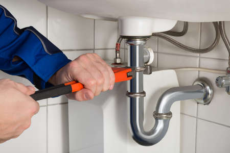 Photo pour Close-up Of Male Plumber Repairing Sink In Bathroom - image libre de droit
