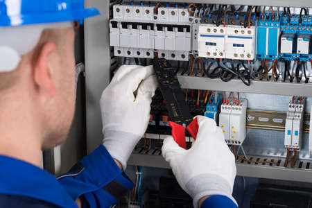 Photo pour Close-up Photo Of Male Electrician Repairing Fusebox - image libre de droit