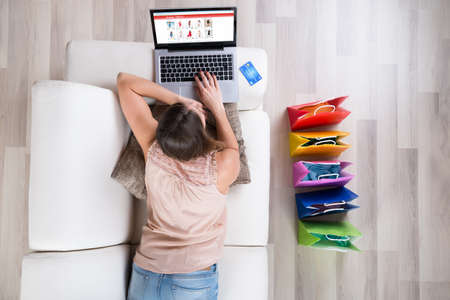 Photo for Young Woman On Sofa Shopping Online With Laptop - Royalty Free Image