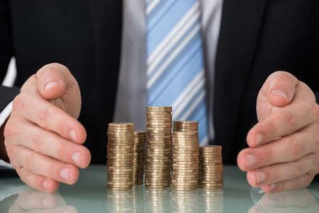 Foto de Close-up Of Businessperson Saving Pile Of Coins - Imagen libre de derechos