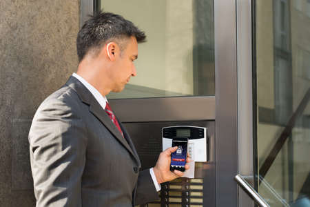 Foto de Mature Businessman Holding Smartphone For Disarming Security System Of Door - Imagen libre de derechos