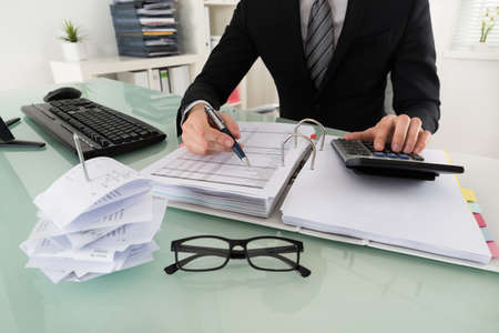 Photo pour Close-up Of Businessman Calculating Tax In Office - image libre de droit