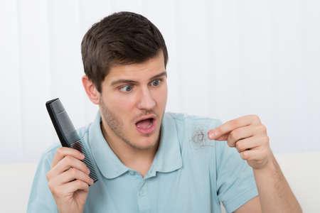 Foto de Young Man Holding Comb Looking At Loss Hair - Imagen libre de derechos