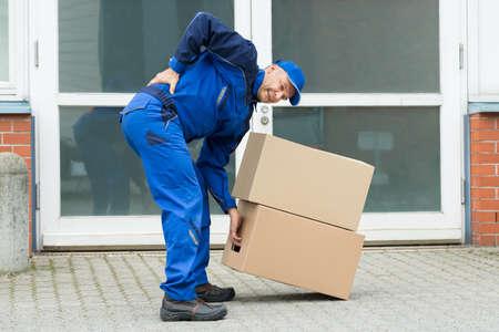 Foto de Delivery Man Suffering From Backpain While Lifting Boxes - Imagen libre de derechos