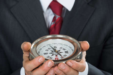 Close-up Photo Of Businessman Hand Holding Compass