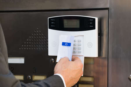 Foto de Close-up Of Businessperson Hands Inserting Keycard In Security System To Unlock Door - Imagen libre de derechos
