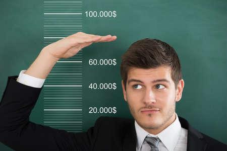 Foto de Close-up Of A Young Businessman Comparing His Salary With Profit - Imagen libre de derechos