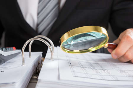 Photo for Close-up Of Young Businessman Hand Examining Invoice With Magnifying Glass - Royalty Free Image