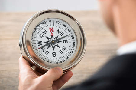 Close-up Of Young Businessman Holding Compass At Desk In Office
