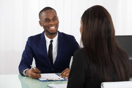 Photo pour Male Manager Interviewing A Young Female Applicant In Office - image libre de droit