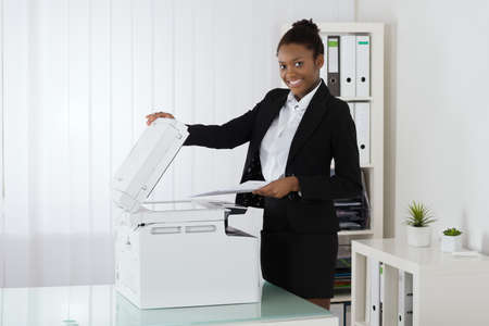 Photo for Smiling Young African Businesswoman Placing Paper On Photocopy Machine In Office - Royalty Free Image
