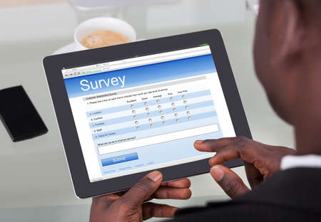 Photo pour Close-up Of A Businessperson Filling Survey Form On His Digital Tablet At Office - image libre de droit