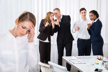 Foto de Businesspeople Gossiping Behind Stressed Female Colleague In Office - Imagen libre de derechos