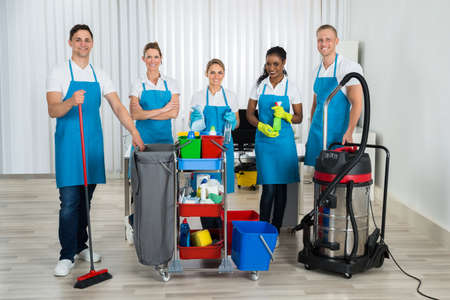 Photo pour Group Of Happy Cleaners Standing With Cleaning Equipments In Office - image libre de droit