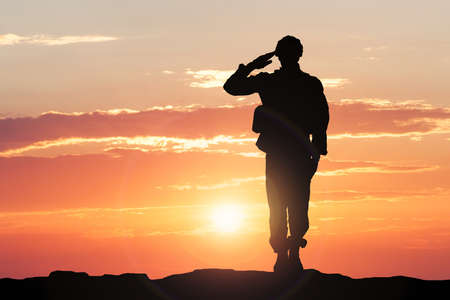 Foto de Silhouette Of A Soldier Saluting During Sunset - Imagen libre de derechos