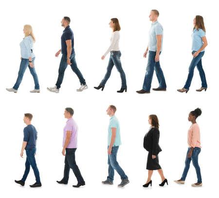 Foto de Group Of People Walking In Line Against White Background - Imagen libre de derechos