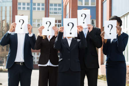 Photo for Group Of Businesspeople Hiding Face Behind Question Mark Sign;Outdoor - Royalty Free Image