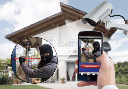 Foto de Person Hand Holding Mobile Phone Detecting Burglar In Security System With Surveillance Camera Behind - Imagen libre de derechos